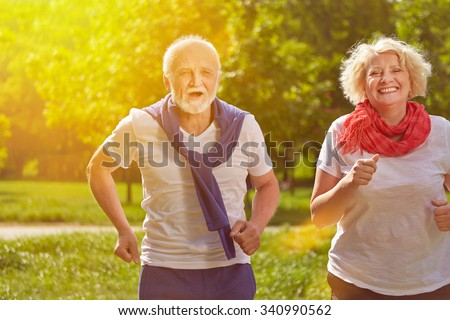 Two active happy seniors running in nature in summer - stock photo
