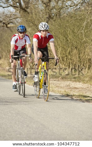 Two active male athletes riding cycles in a rural area - stock photo