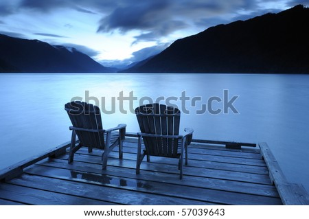 Two adirondack chairs on a deck  at sunset