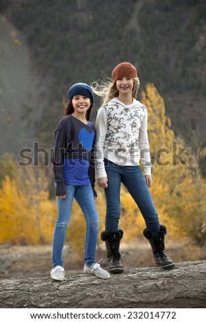 Two Adolescent girls standing on log in outdoor autumn setting - stock photo