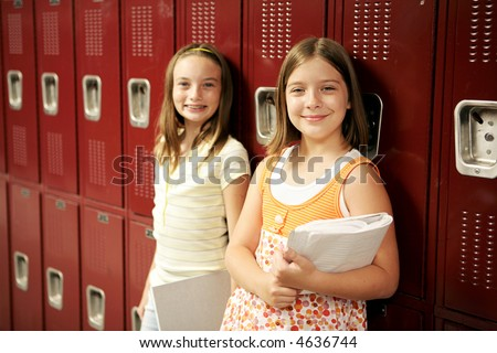 Two adolescent school girls in front of their lockers. - stock photo
