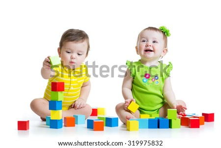 Two adorable babies kids playing with educational toys. Toddlers girl and boy sitting on floor. Isolated on white background. - stock photo
