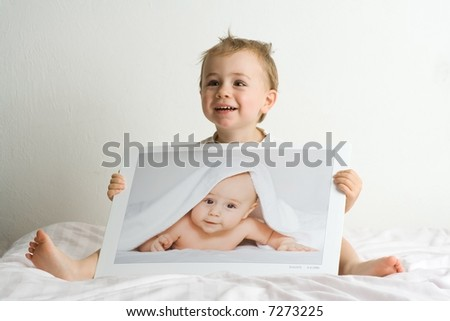 Two adorable blond little boys; one is two years old, the other is infant. Unclear whether image of infant is photo or illusion to look like photo.one and the same boy (yearling,two years old)