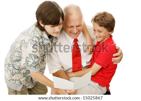 Two adorable boys giving their father a greeting card.  Perfect for Fathers Day or other special occasion. - stock photo