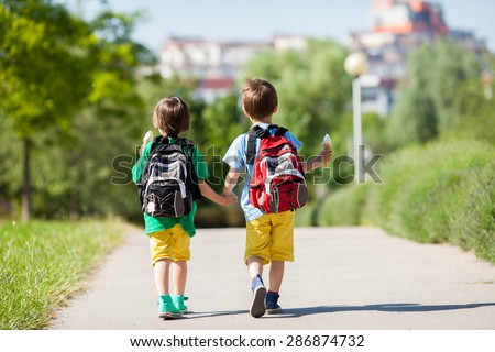 Two adorable boys in colorful clothes and backpacks, walking away, holding and eating ice cream on a sunny summer afternoon, warm day, casual clothing - stock photo