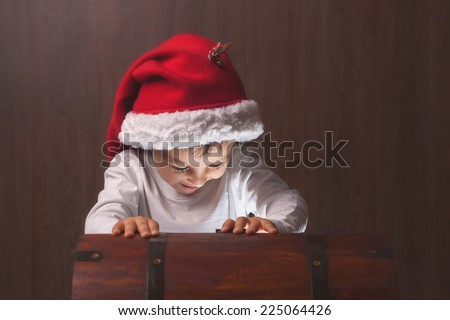Two adorable boys, opening wooden chest, glowing light from inside, happy kids with santa hats - stock photo
