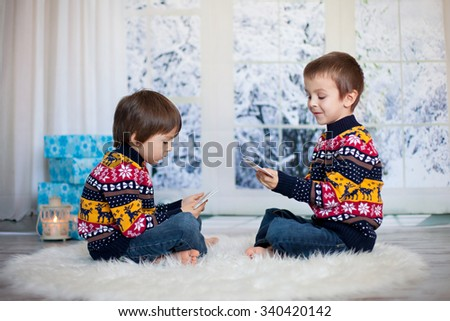 Two adorable children, boy brothers, playing cards at home, wintertime, christmas decoration around them, snowy day behind the window - stock photo