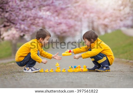 Two adorable children, boy brothers, playing in park with rubber ducks, having fun. Childhood happiness concept - stock photo