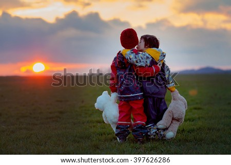 Two adorable children, boy brothers, watching beautiful splendid sunset over a green field, holding teddy bears,springtime - stock photo