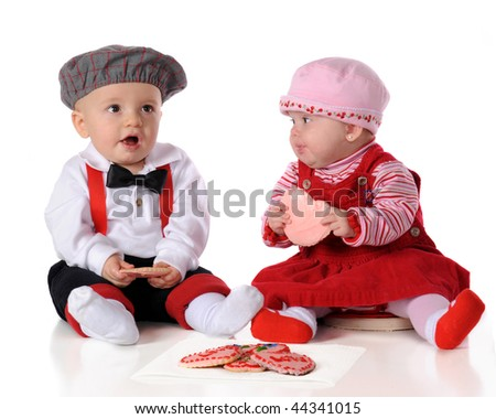Two adorable dressed-up babies snacking together on heart-shaped cookies.  Isolated on white. - stock photo