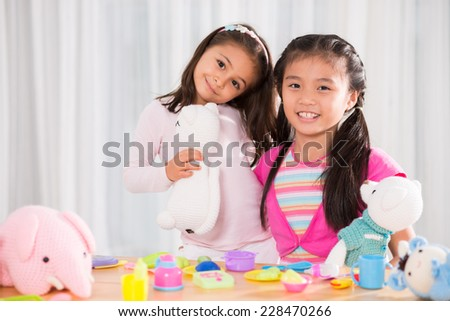 Two adorable girls enjoying playing together - stock photo