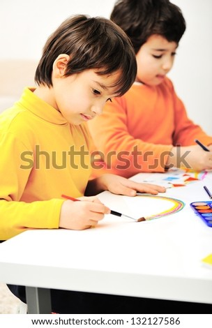 two adorable happy children drawing with crayons