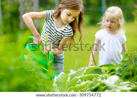 Two adorable happy little girls watering plants and flowers in the garden on warm and sunny summer day - stock photo