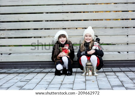 Two adorable kid girl friends in white hats and pattern black jackets has fun outdoor  at the winter day - stock photo