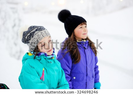 Two adorable kid girls in warm colorful clothes walking in the snowy park on beauty winter day - stock photo