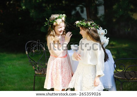 Two adorable kid girls with flower wrearth having tea in the garden. Retro style - stock photo