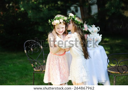 Two adorable kid girls with flower wreath having tea in the garden. Retro style - stock photo