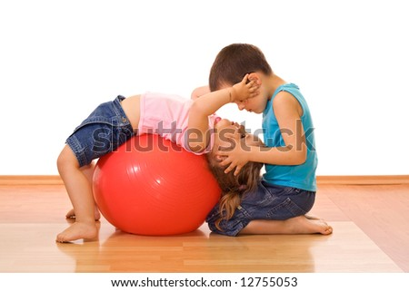 Two adorable kid playing with a large rubber ball on the floor - stock photo
