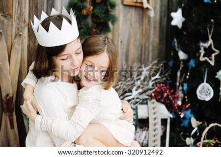 Two adorable kid school aged sisters near th tree in a cozy home celebrating Christmas - stock photo
