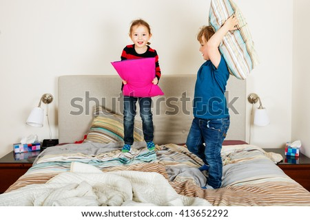 Two adorable kids having pillow fight on the bed - stock photo