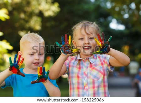 Two adorable kids with hands covered in paint