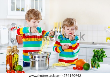 Two adorable little boys preparing healthy meal with spaghetti and fresh vegetables in domestic kitchen, indoors. Sibling children in colorful shirts. - stock photo