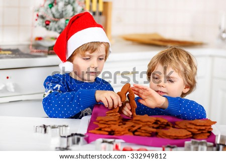 Two adorable little friends baking gingerbread cookies. Happy kid boys, children in blue xmas pullovers. Playing and having fun. Kitchen decorated for Christmas. Family, holiday, kids lifestyle - stock photo