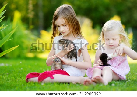 Two adorable little girls feeding small kittens with kitten milk from the bottle at summer day - stock photo