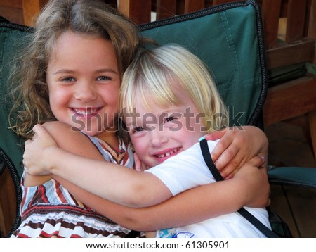 two adorable little girls smiling and hugging - stock photo
