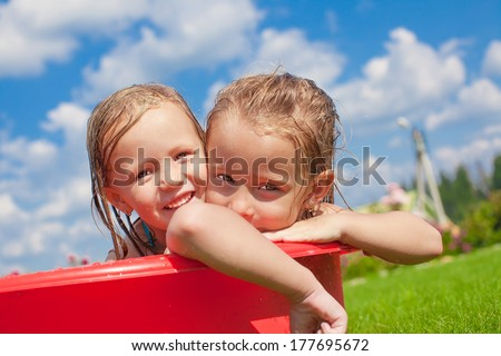 Two adorable little happy girls having fun outdoor on summer day background blue sky