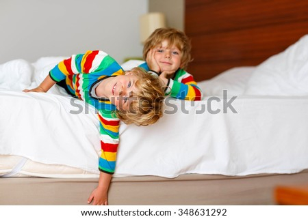 Two adorable little sibling kid boys having fun in bed after sleeping at home, indoor. Brothers smiling at the camera. Family, vacation, childhood concept. Selective focus on one child - stock photo