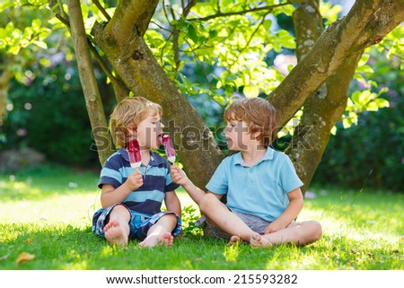 Two adorable little sibling kids eating ice cream pops in home's garden, outdoors. Feeding each other. - stock photo