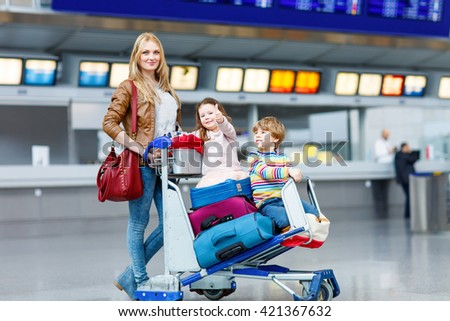 Two adorable little siblings, kid boy and girl sitting on suitcases on international airport. Young mother pushing. Brother and sister, happy family wating for flight and going on vacations. - stock photo