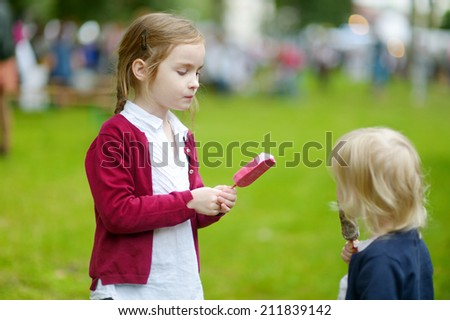 Two adorable little sisters eating an ice cream outdoors on beautiful summer day - stock photo