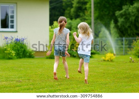 Two adorable little sisters having fun outdoors on warm and sunny summer day - stock photo