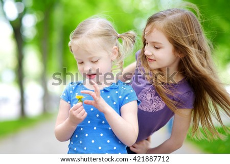Two adorable little sisters laughing and hugging each other on warm and sunny summer day - stock photo