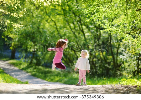 Two adorable little sisters laughing and jumping on warm and sunny summer day - stock photo