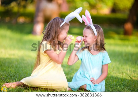 Two adorable little sisters playing with eggs wearing bunny ears on Easter day - stock photo