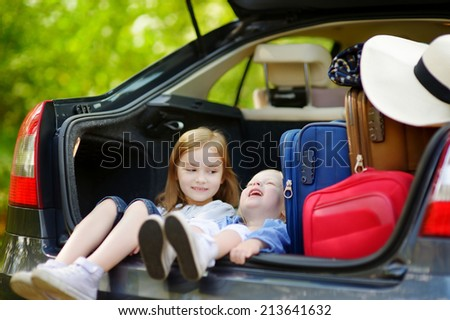 Two adorable little sisters sitting in a car just before leaving for a car vacation with their parents