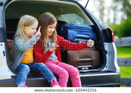 Two adorable little sisters taking photo of themselves before going on vacations with their parents. Two kids sitting in a car ready to travel. Active leisure with small kids.
