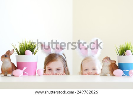 Two adorable little sisters wearing bunny ears on Easter day - stock photo