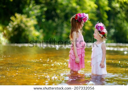 Two adorable little sisters wearing flower crowns by a river on warm and sunny summer day
