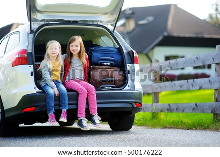 Two adorable little sitting in a car before going on vacations with their parents. Two kids looking forward for a roadtrip or travel.
