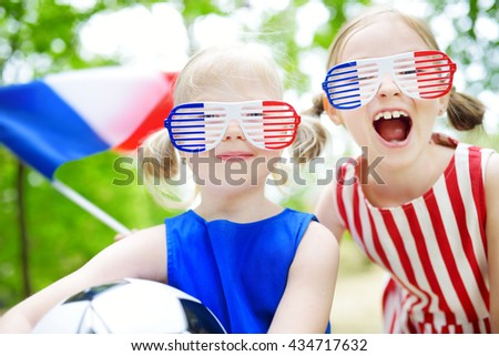 Two adorable little soccer fans cheering on summer day - stock photo