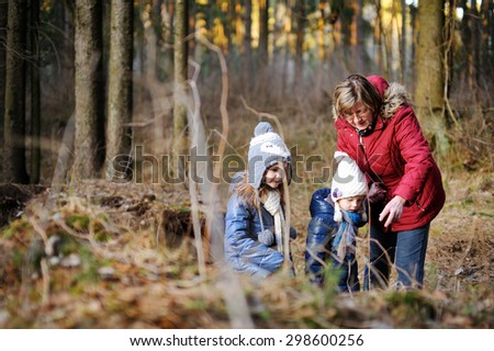 Two adorable sisters and their grandmother taking a walk on autumn forest - stock photo