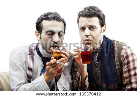 Two adult man wearing old-man clothes and makeup, sitting on a used vintage sofa. Looking rather cold and pitiful they are both warming themselves with a glass of hot tea. Isolated on white background - stock photo