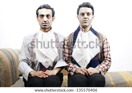 Two adult man wearing old-man clothes and makeup. They both wear napkins on their necks, gazing into space and waiting patiently for their coming meal. Isolated on white background. - stock photo