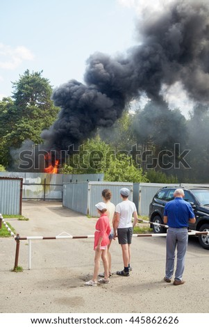 Two adults and two children watch at big fire and black smoke behind fence made of corrugated steel sheets.