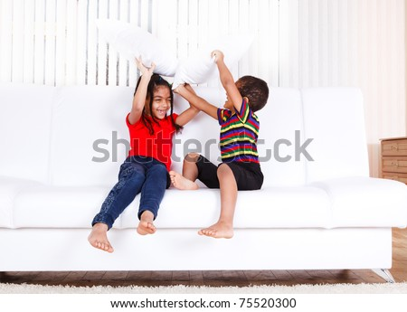 Two african american kids playing with pillows - stock photo