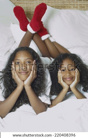 Two African American sisters on bed - stock photo